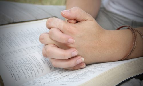 Hands-Closed-in-Prayer-on-top-of-Open-Bible-182787069_web