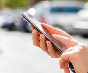 Woman-looking-for-car-with-mobile-phone-in-parking-lot-511025876_web